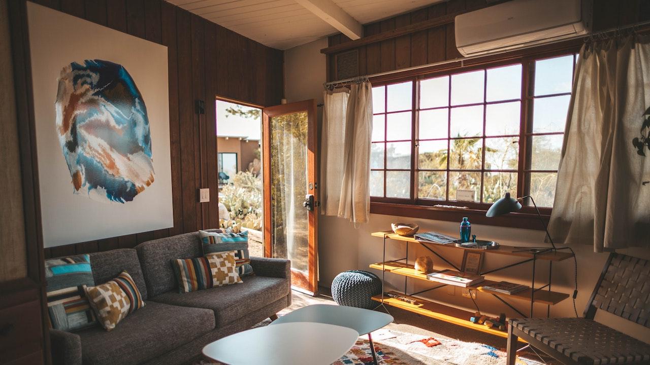 大きな窓とアートとソファーのある部屋の無料バーチャル背景素材