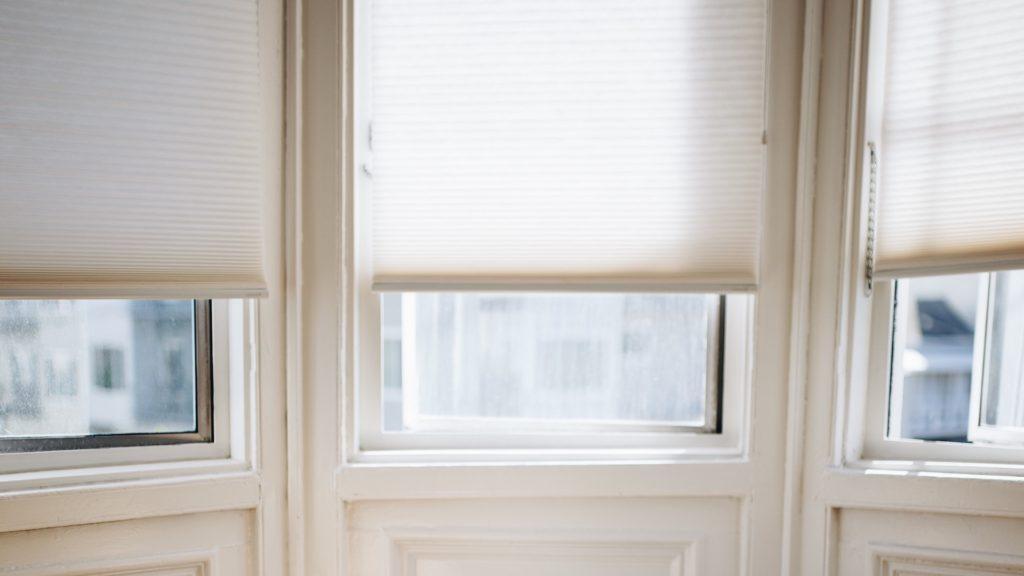 白いロールスクリーンのかかる窓の無料バーチャル背景素材
