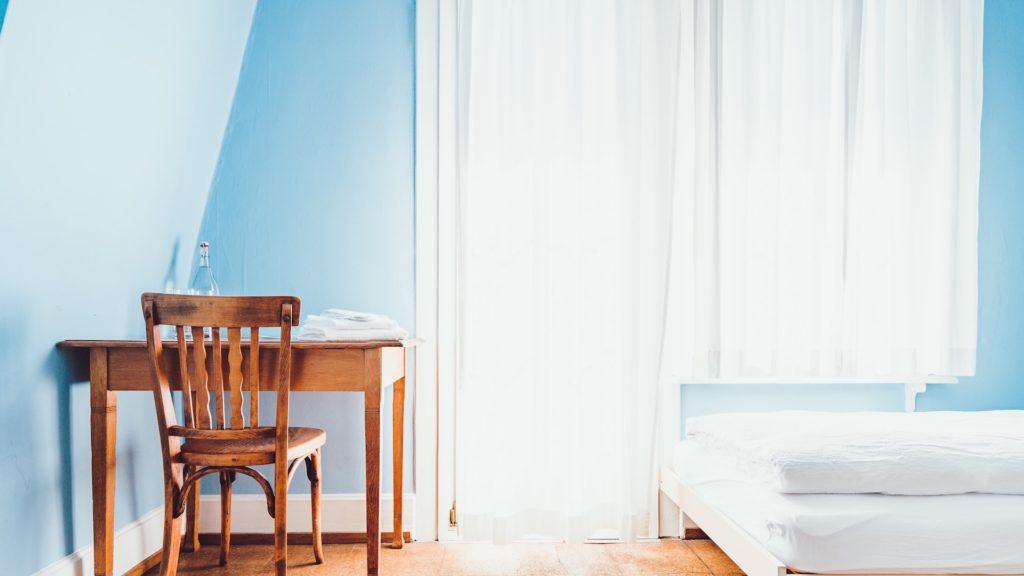 水色の壁と机と白いカーテン