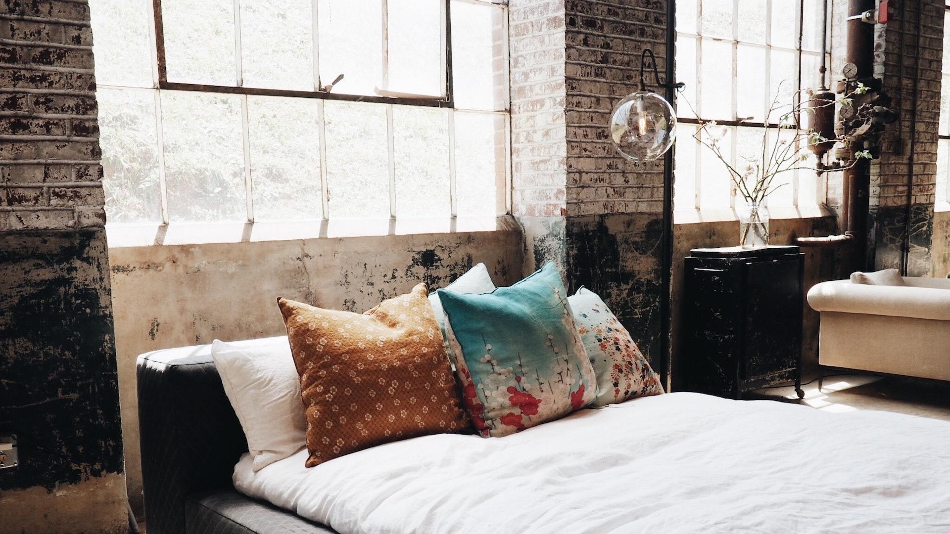 大きな窓とベッドとクッションのある部屋