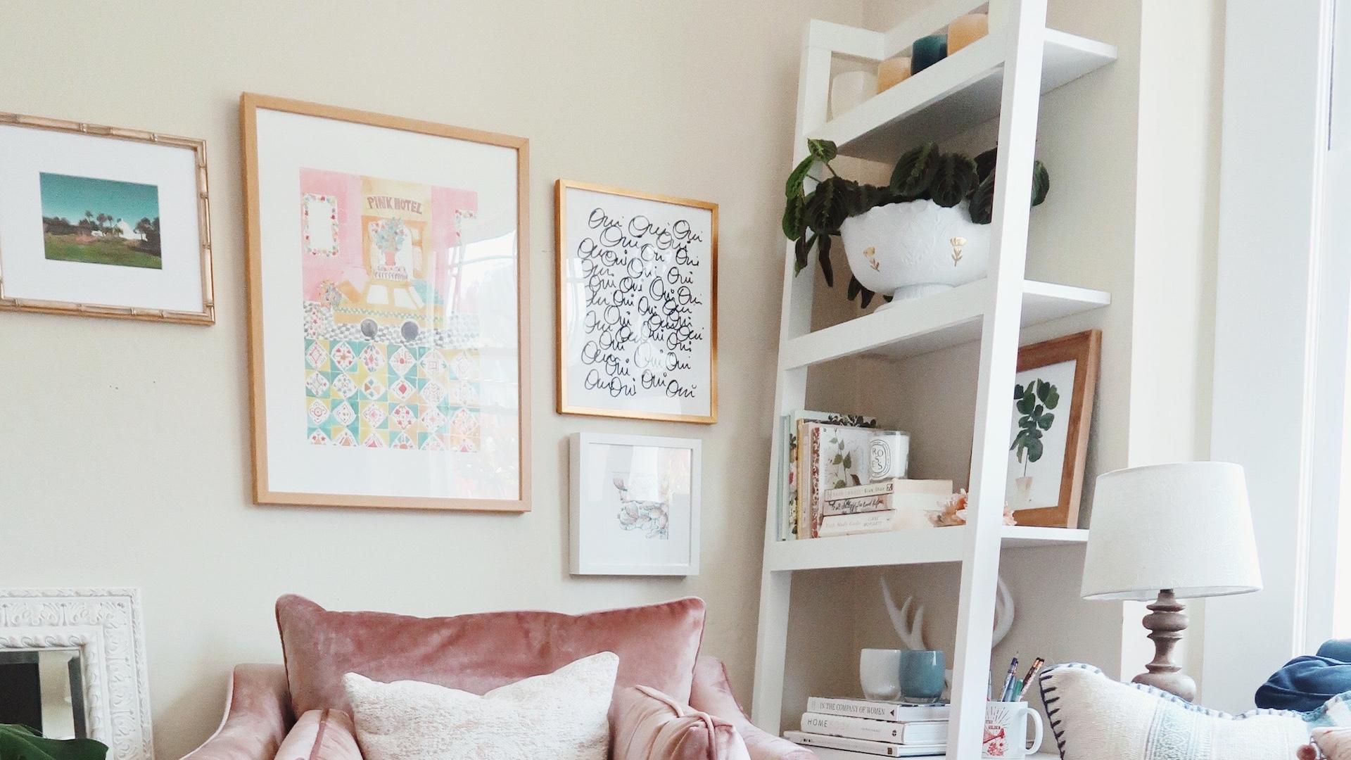 ピンクのソファーと白いシェルフのあるかわいい部屋
