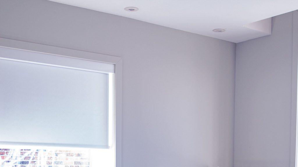 ロールスクリーンのある白い壁の部屋