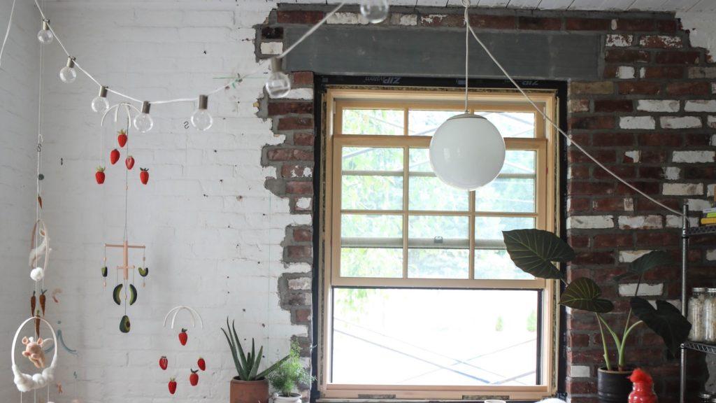 レンガの壁と窓とモビールのある部屋