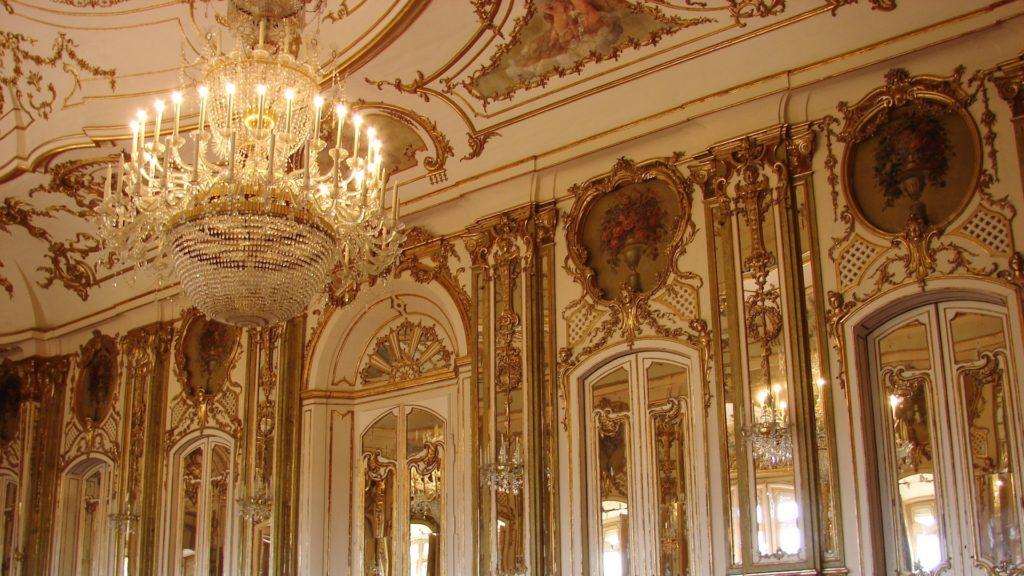 ゴールドの壁とシャンデリアのある部屋