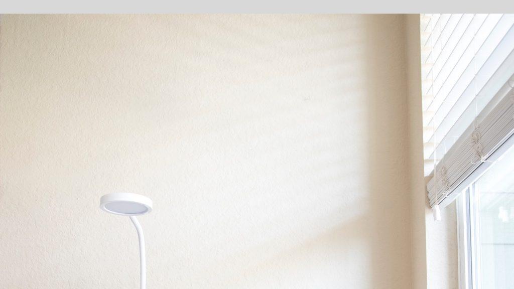 白いテーブルライトとブラインドカーテンのある部屋