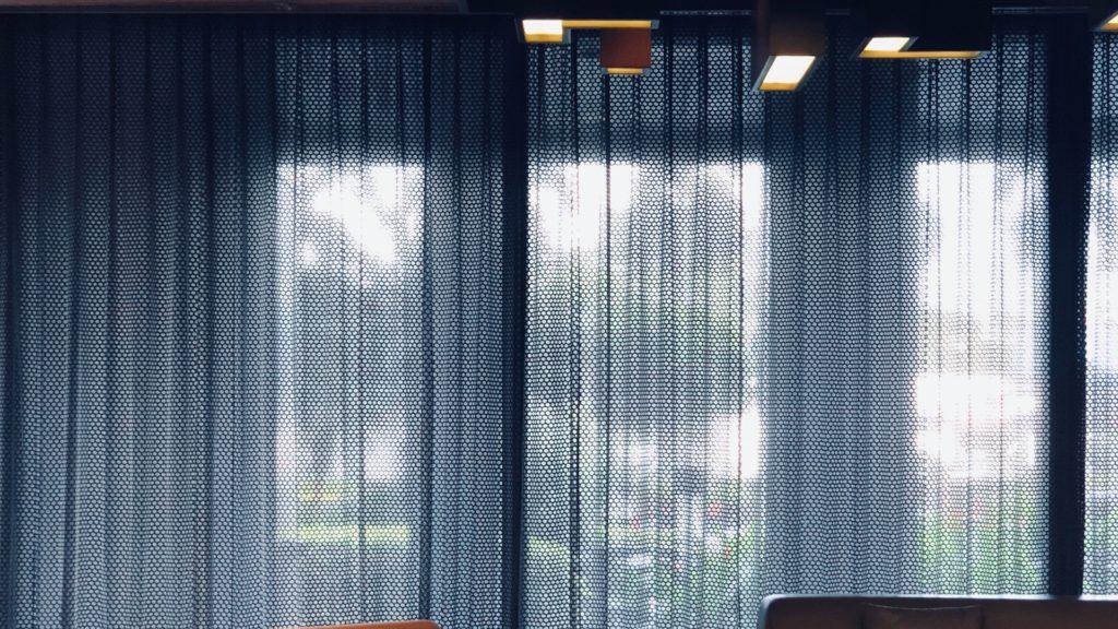 青いカーテンのかかる大きな窓のある部屋